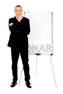 Male executive standing near flip chart