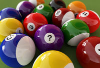 Group of billiard balls with numbers, on green carpet table.