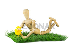 Wooden mannequin lying on lawn with plush chicken