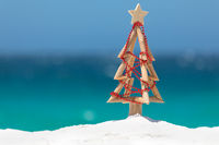 Driftwood Christmas tree decorated with string of red baubles at beach summer