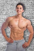Fitness Bodybuilder Bodybuilding Muskeln Mann Wand stark muskulös jung schaut nach oben