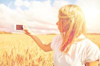 close up of girl with smartphone on cereal field