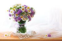 Chamomiles bouquett in vase on fabric background.