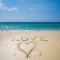 Love written on the beach over sea