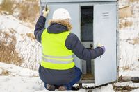 Railroad worker checking electrical enclosures