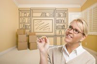 Female Holding Pencil In Room With Drawing of Entertainment Unit