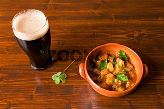 Traditional Irish Stew with a pint of stout beer and a shamrock