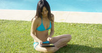 Young woman using a tablet at  resort pool
