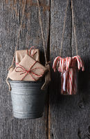 Presents in a bucket and Candy Canes in a Jar hanging on Rustic Wall.