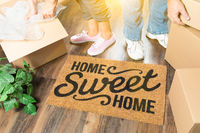 Man and Woman Unpacking Near Home Sweet Home Welcome Mat, Moving Boxes and Plant