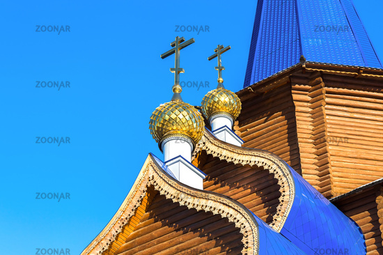 Golden domes with crosses on wooden orthodox church against the blue sky in Samara, Russia