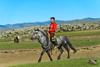 Junge reitet auf einem Pferd durch die Steppe