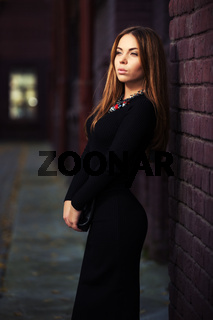 Young fashion woman in black dress at the brick wall