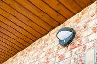 Modern wall lamp with motion and light sensor on the brick wall