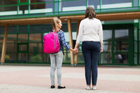 elementary student girl with mother at school yard