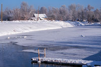 Altai russian country village Talitsa under winter snow on bank of river with gangway over water