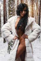Naked brunette wearing white fur coat posing in a snowy forest