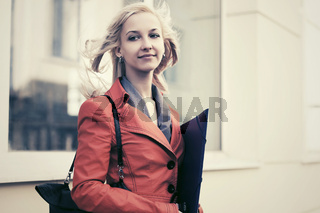 Young fashion business woman with a folder against office building