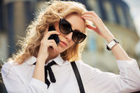 Fashion business woman in sunglasses calling on mobile phone