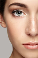 Closeup macro portrait of female face. Human woman half-face  with day beauty makeup. Girl with perfect skin and freckles