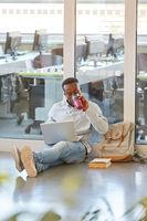 Afrikanischer Student mit Laptop und Kaffee