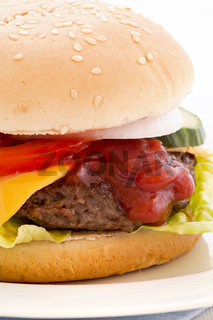 American cheeseburger stuffed with beef patty und cheddar as closeup on white background