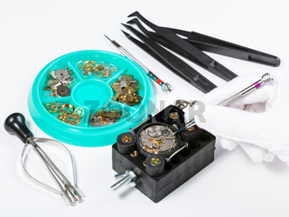 repairing old mechanical watch on white table