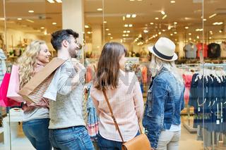 Junge Leute beim Shopping vor Modeladen
