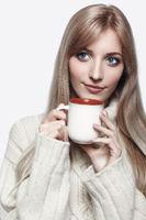 Blonde woman drinking a cap of tea