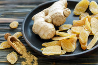 Ginger root and candied ginger on a wooden plate.