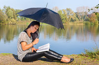 Woman with umbrella reading book in nature