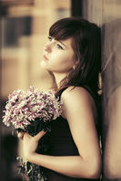 Sad young woman with a flowers standing at the wall