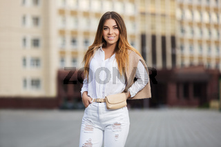 Young fashion woman in white blouse and ripped jeans walking in city street
