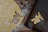 Top view of a baking sheet with a moose shaped cookie, with dough and additional moose shapes in raw