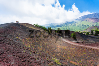 tourists walk on ridge between old crater