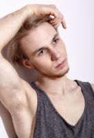 Young blonde man in shirt posing