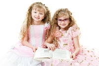 Twin princesses reading a book