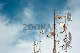 Antennas on a roof against cloudy sky background