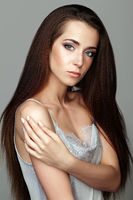 Beauty portrait of young woman. Brunette girl with long hair and day female makeup on gray background
