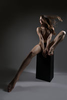 Pretty slim blonde topless sitting on a black cube