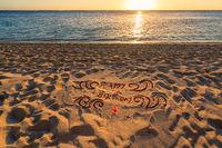 handwritten happy birthday on sand beach