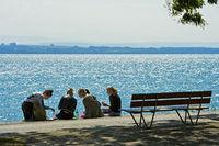 Young women during the lunch break on the shore of lake Neuchatel, Neuchatel, Switzerland