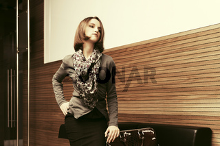 Young fashion business woman sitting on a couch in office interior