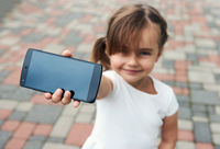 Adorable little girl with a smartphone outdoors