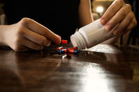 Woman get out pills from white plastic bottle on pilished table