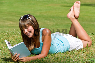 Smiling young woman lying down on grass with book