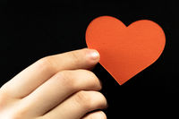 Female hands touching red paper heart shape by finger on black background