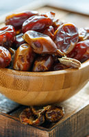 Delicious dried dates in a wooden bowl.
