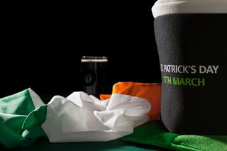 St Patrick day with a pint of black beer, hat and irish flag over a green table