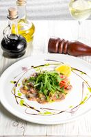 Salmon carpaccio with arugula leaves and sticky balsamic vinegar